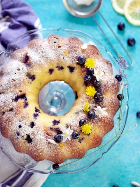 vertical image of blueberry lemon pound cake showing the entire baked cake