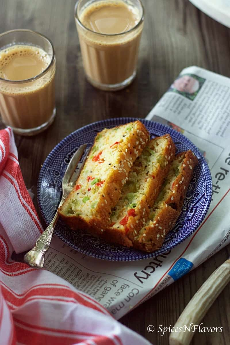 3 slices of cake placed on a blue plate alongwith a newspaper and tea in the background