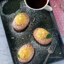 vertical image of lemon friands with lemon curd on top