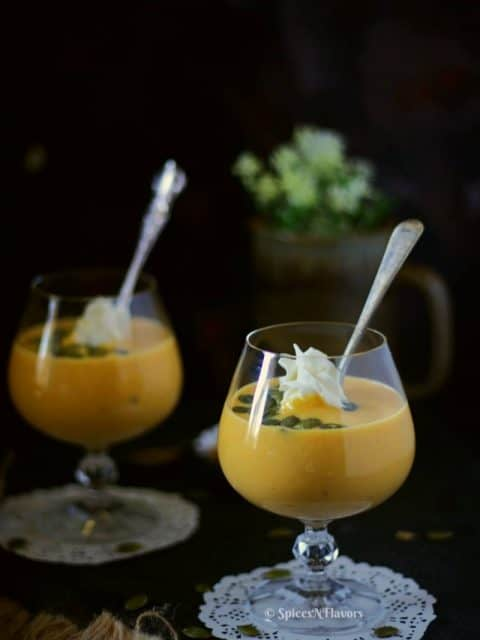 pumpkin custard served in glasses with whipped cream pumpkin seeds and a spoon in the picture