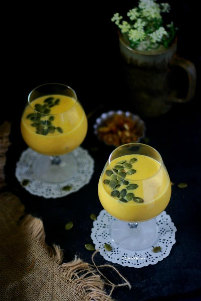 pumpkin custard or kaddu ki kheer served in a glass with pumpkin seeds shot in a straight on mode.