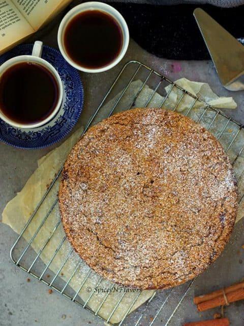 overhead image of apple crumb cake with black tea and books