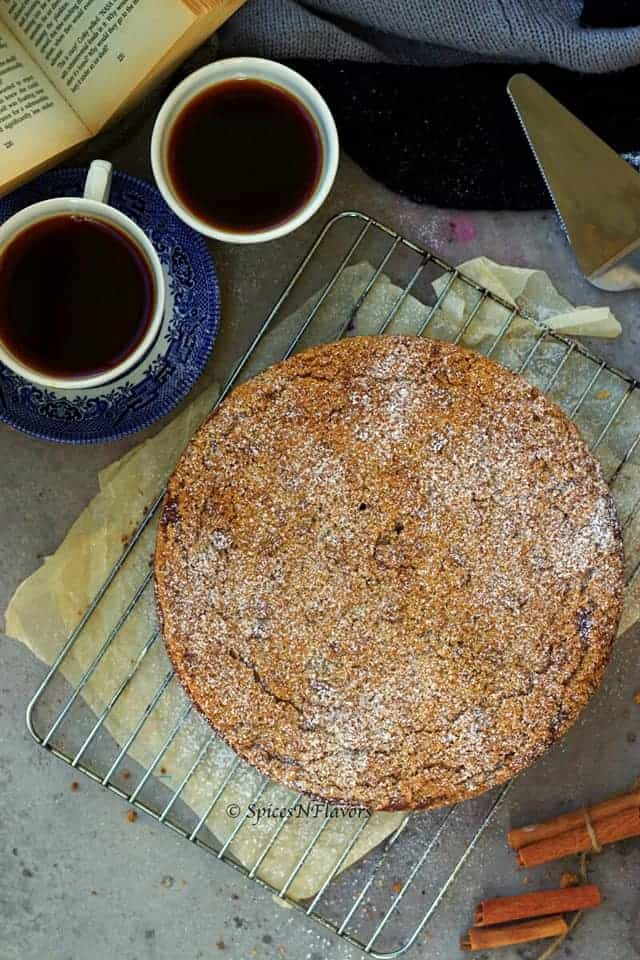 overhead image of apple crumb cake with black tea and books