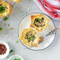 two pieces of spinach and feta filo cups or spanokopita served on a plate