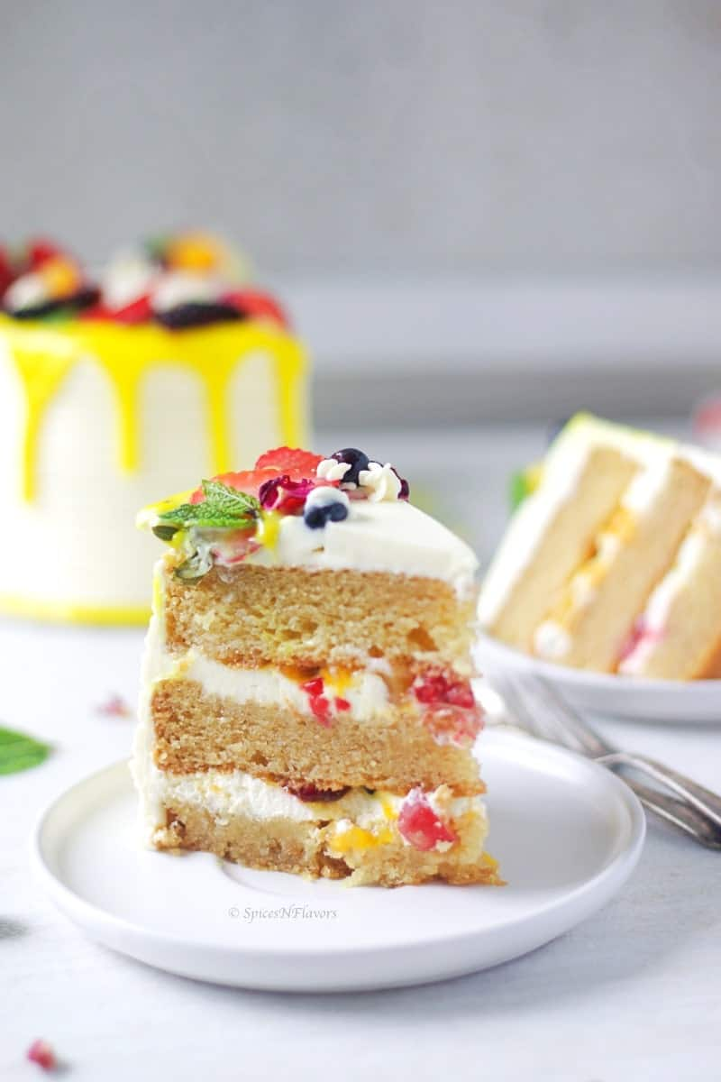 cut slice of Fresh Fruit Cake showing the inner texture of the cake with whipped cream and fruits