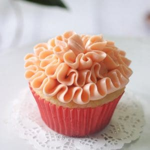 strawberry filled cupcake with a ruffle pattern placed on a small white lace dollie
