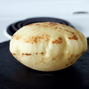 puffed up image of pita bread cooked on stovetop