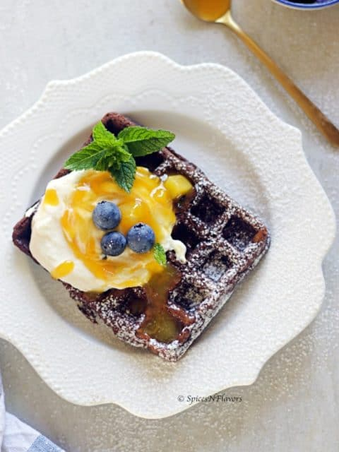 chocolate waffles topped with whipped cream and passionfruit mango compote