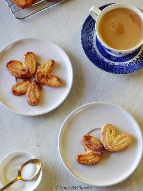palmier cookies served on a white plate along with evening cup of tea
