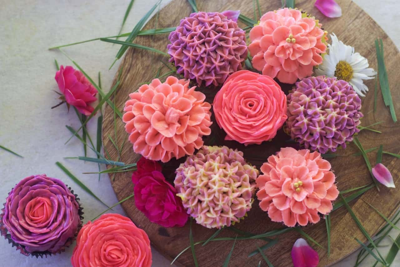 overhead view of buttercream flowers arranged on a wooden board