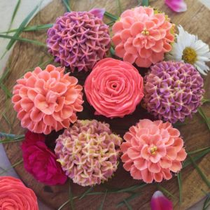 close up view of 7 buttercream flowers placed adjacent to each other forming circle