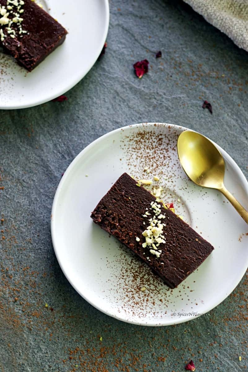 slice of instant pot chocolate terrine served in a white round plate with a golden spoon