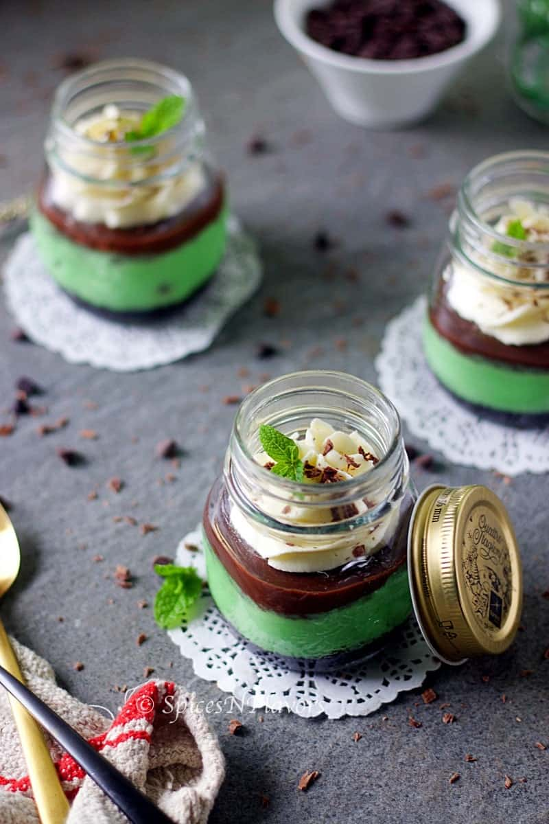 instant pot mint cheesecake jars placed in a triangle shape showing the garnishes on top