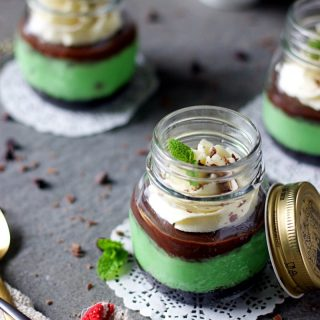 instant pot mint cheesecake jars placed in a way showing the layers of the dessert