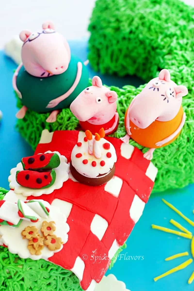 image showing fondant accents of peppa pig and family along with picnic basket placed on peppa pig birthday cake