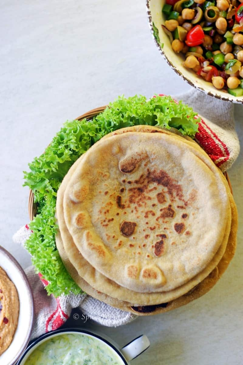 overhead view of whole wheat pita bread placed in a brown basket with lettuce on sides