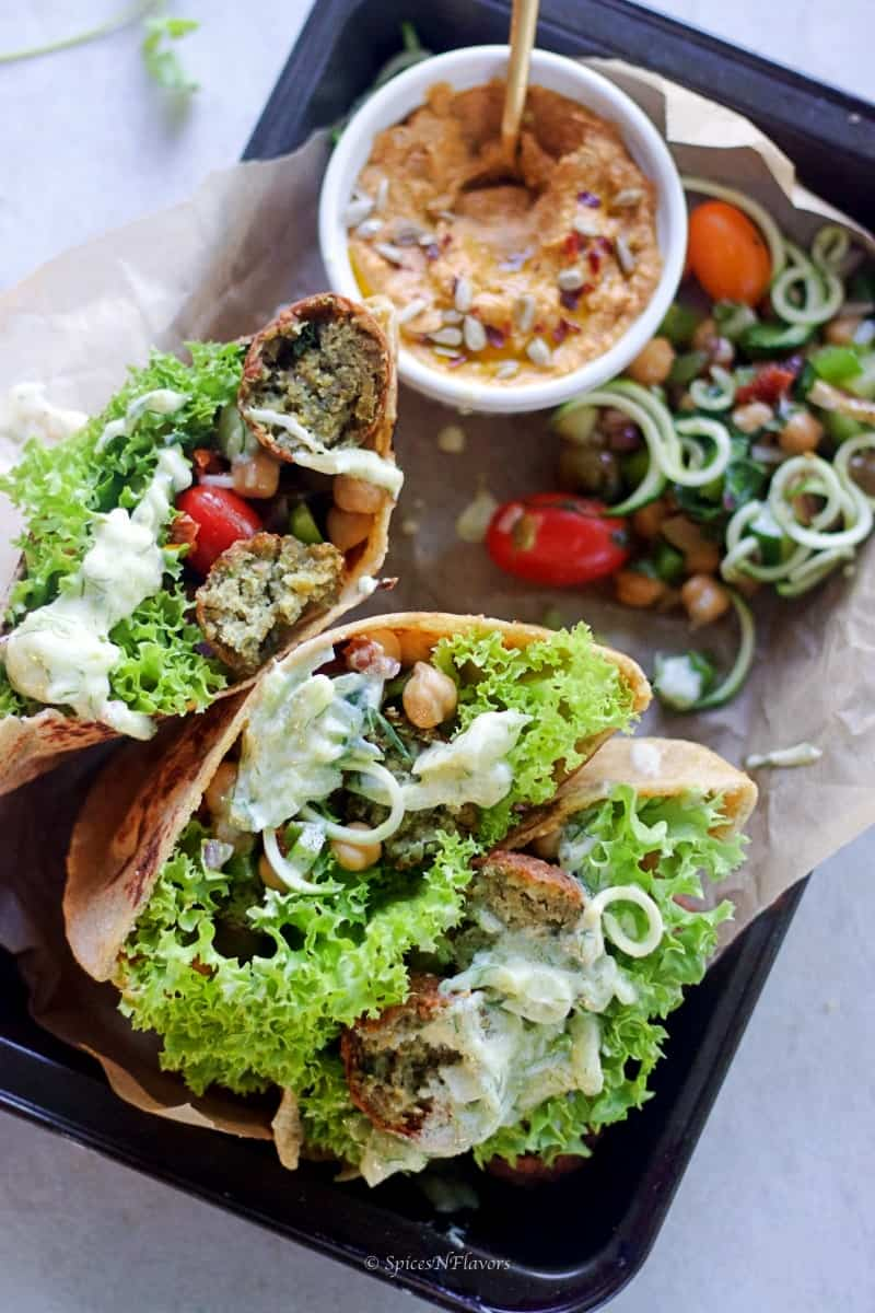 whole wheat pita bread pockets filled with salad, hummus, falafel and sauce