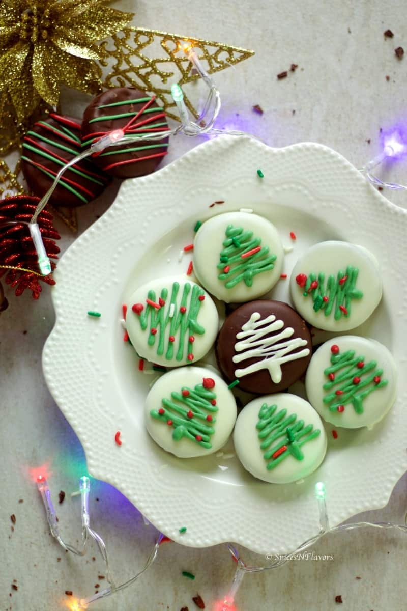 oreo cookies dipped in white chocolate arranged in a plate and surrounded by christmas decorations and lights