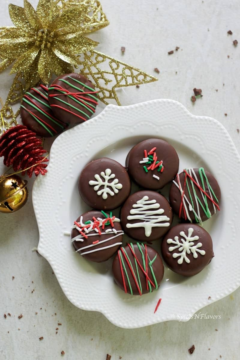 oreo cookies dipped in dark chocolate arranged in a plate and surrounded by christmas decorations