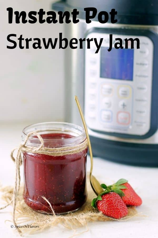 A small jam full of strawberry jam made in the instant pot with two fresh strawberries on the side and instant pot in the background