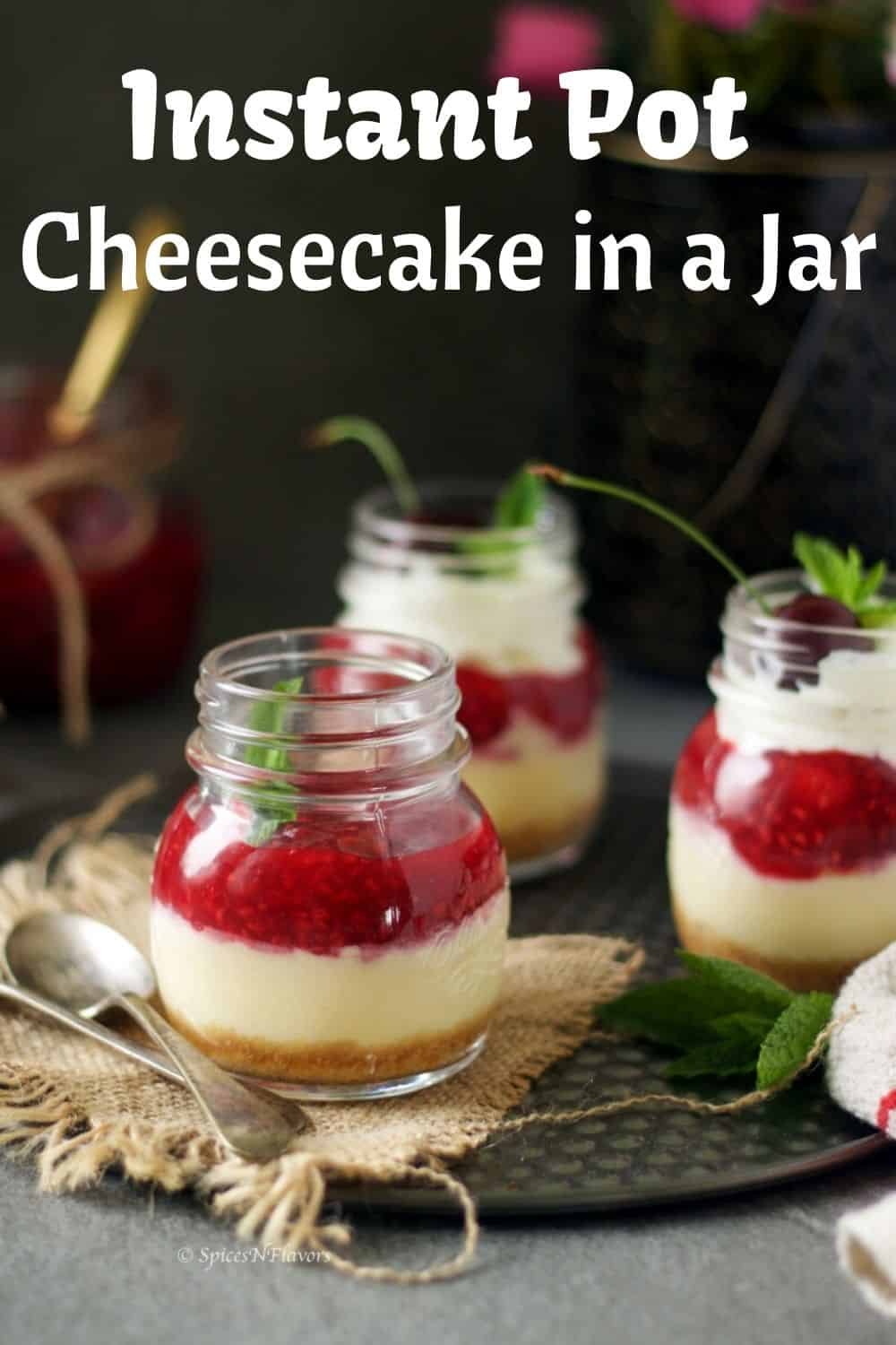 new york style cheesecake made in mason jars. 3 of them with strawberry sauce in the background