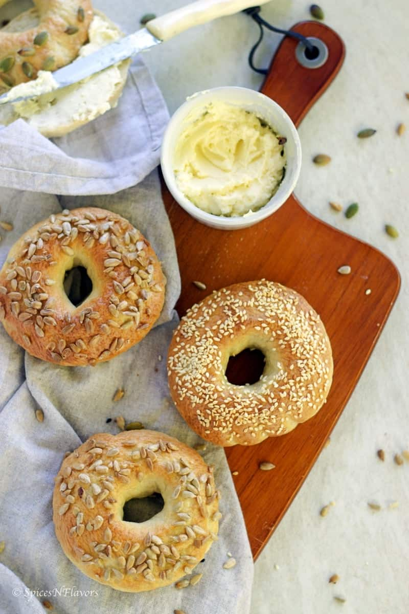 3 bagels placed on a wooden board with cream cheese spread on the side
