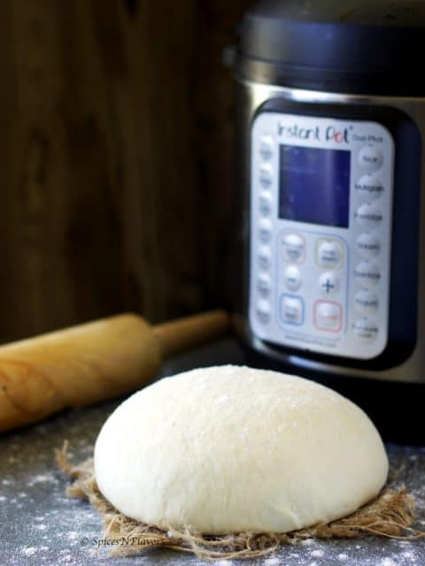 proofed bread dough placed on a towel with a rolling pin and instant pot in the background