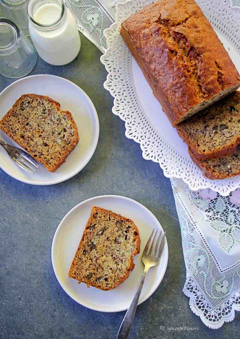 banana bread slices placed on a plate along with the whole bread on one side and milk on the other side