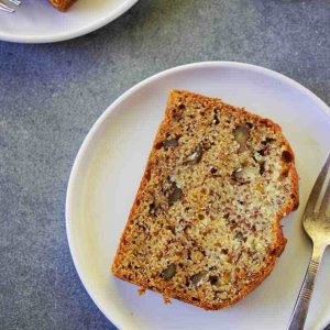 close up overhead image of banana bread slice placed on a white plate with a fork on the side
