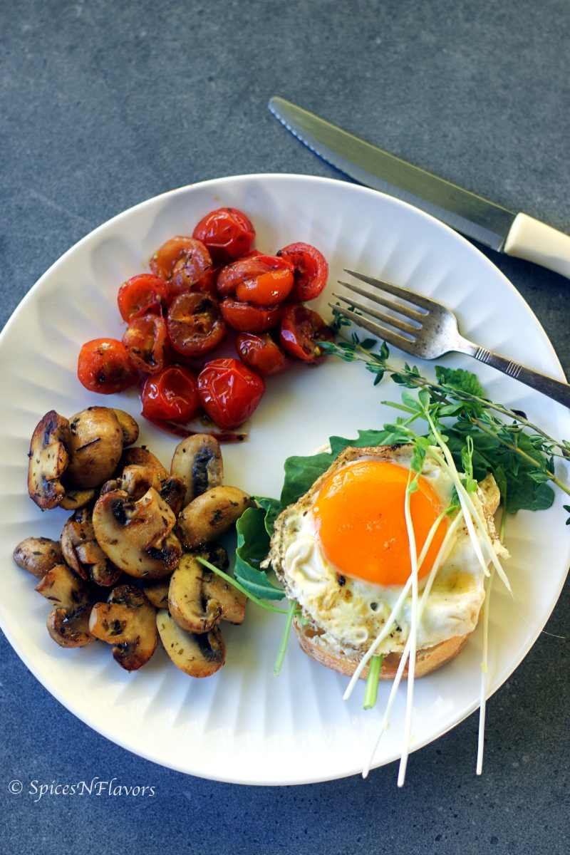 sauteed mushrooms, tomatoes, bread, eggs and greens placed on a white plate