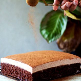 dusting cocoa powder on chocolate cake