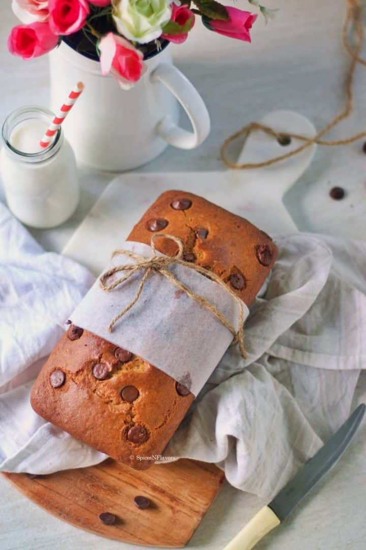 eggless chocolate chip cake wrapped in a parchment paper and placed on a cutting board