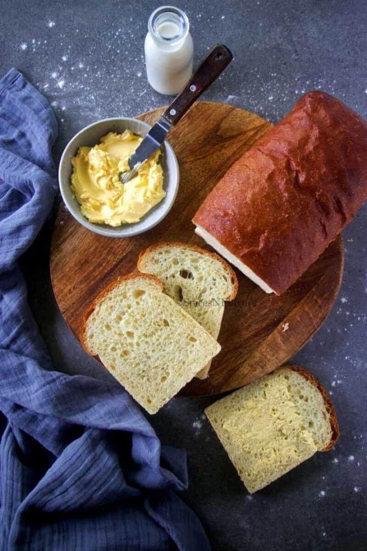 semolina bread slices placed on a wooden chopping board with some butter on the side