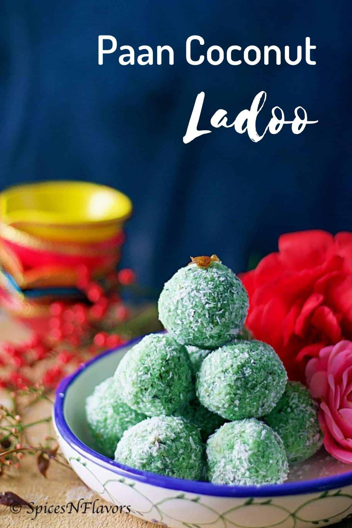 ladoos stacked on each other sitting on a blue rim bowl