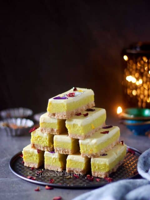burfi bars stacked on each other with lights in the background