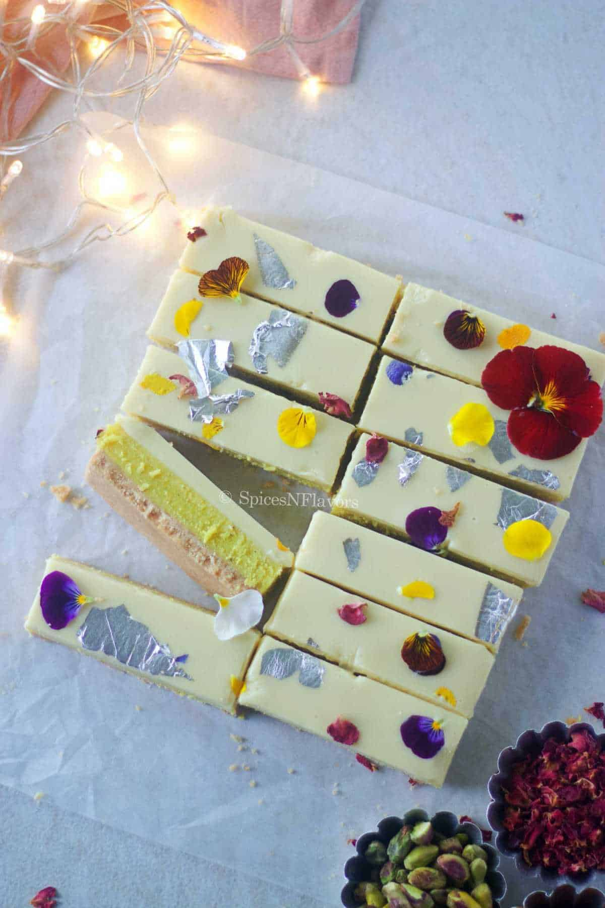 overhead image of burfi bars placed on a white parchment paper to show the decoration of edible flowers on top