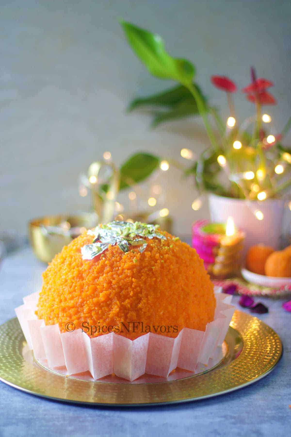 ladoo shape cake placed on a golden plate with lights and plant in the background