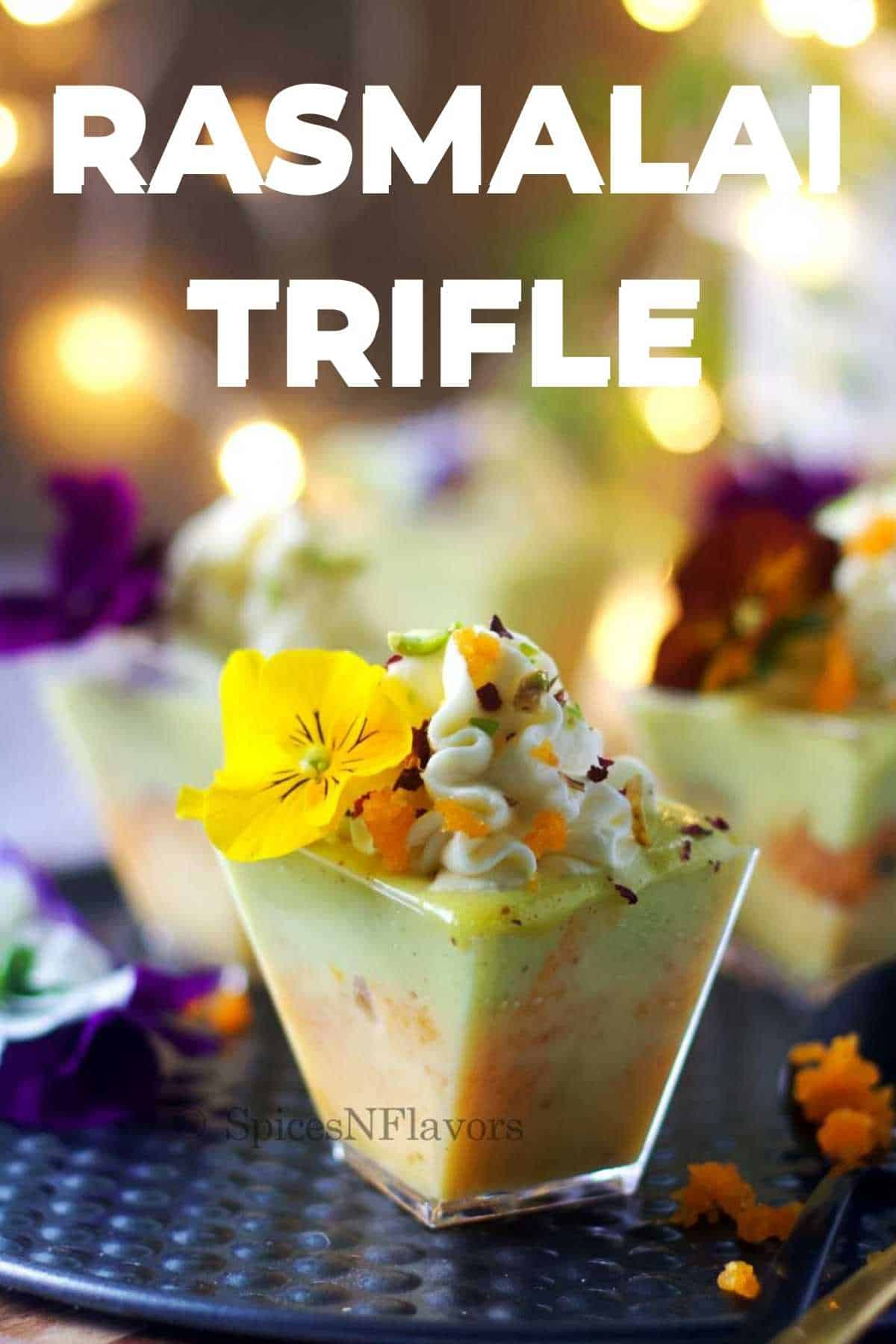 3 Rasmalai Trifle shot glasses placed on a cake tray with lights in the background
