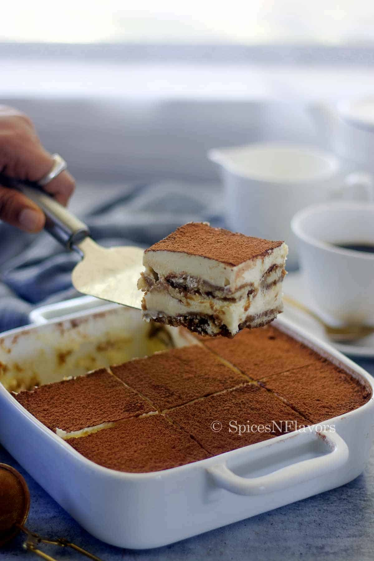 slice of tiramisu held using a serving knife to show the layers within