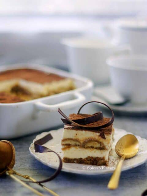 slice of eggless tiramisu placed on a white plate with a golden spoon on the side