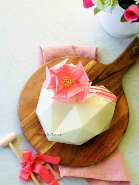 chocolate heart cake placed on a wooden serving board with a hammer on the side