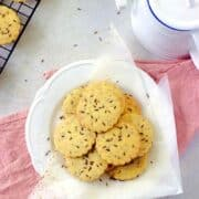 biscuits placed on a white plate with a pink tea towel at the base and tea in the background