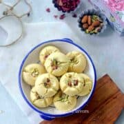 nankhatai biscuits placed in a wide mouth bowl over a marble cutting board with rose petals and nuts on the side
