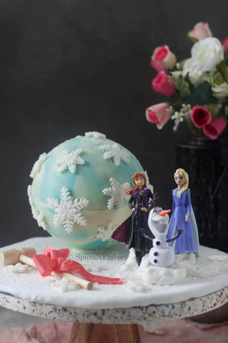 frozen theme pinata cake placed on a cake board with frozen movie characters in the front