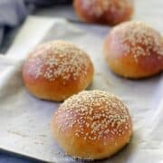 4 burger buns placed diagonally on a baking tray that has been lined with parchment paper