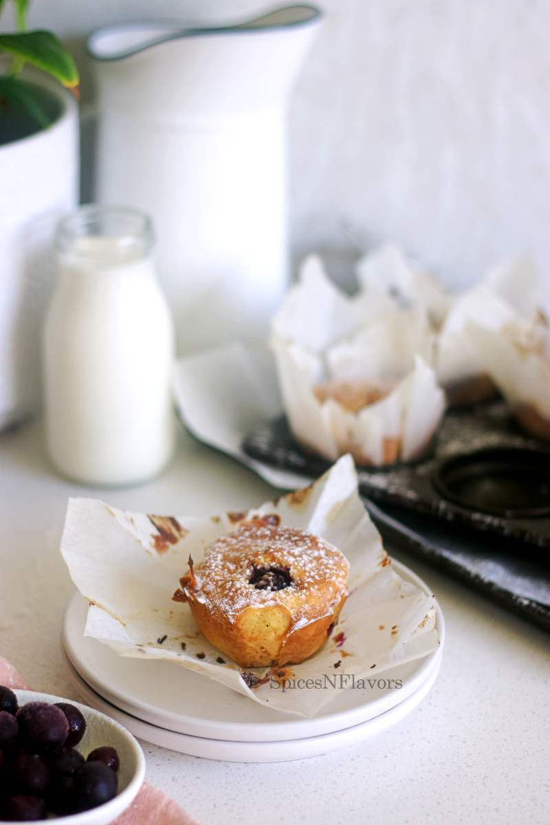 muffin piece placed on a white plate with milk, muffin tray and plant in the background