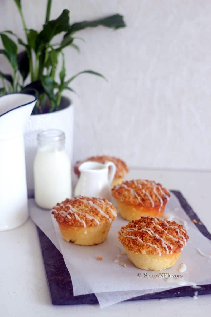 lemon crumb muffins placed on a stone tile with plants and milk in the background