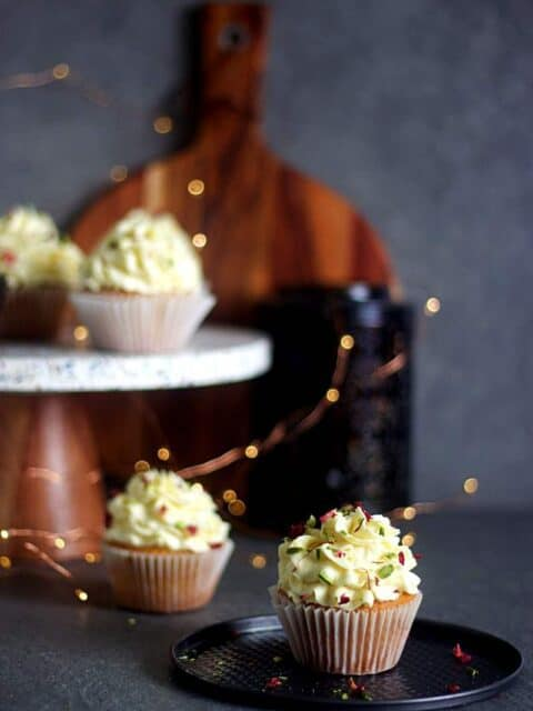 almond cupcakes frosted with milk powder burfi frosting placed on a cake pan with more cupcakes in the background