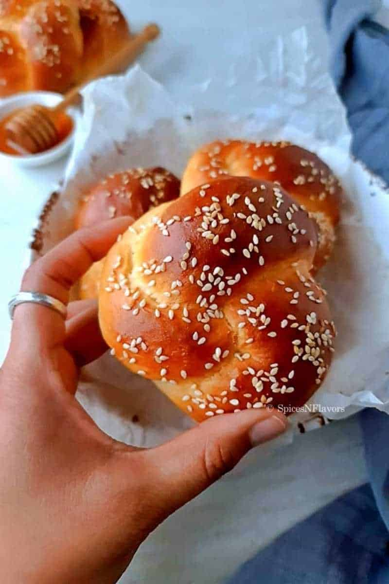 close up image of beautifully baked challah roll held in human hands