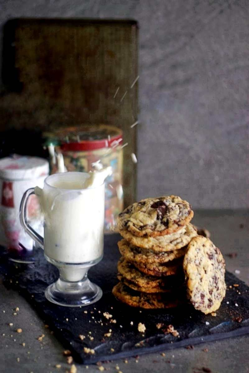 chocolate chip cookies placed one on top of other with a glass of milk on the side